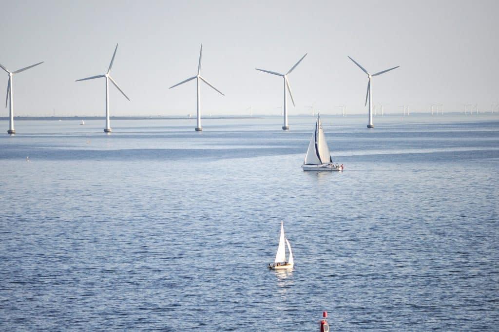 Un parc éolien en mer avec des bateaux de plaisance