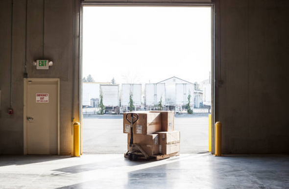 Entrée d'un entrepôt industriel avec un chariot plein de cartons