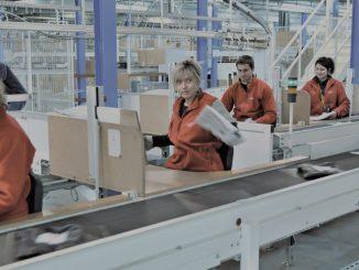 Employés de C-Log qui travaillent sur une chaîne logistique et qui préparent des colis à l'expédition