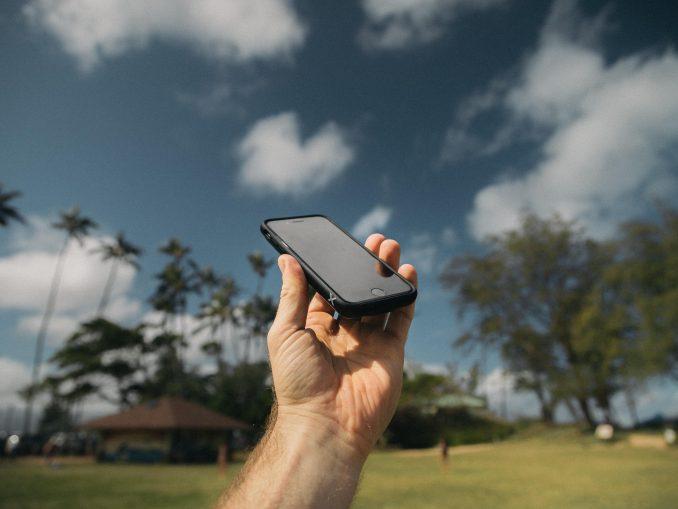 Personne qui tient dans sa main un téléphone portable sur un fond de cocotiers et de ciel bleu