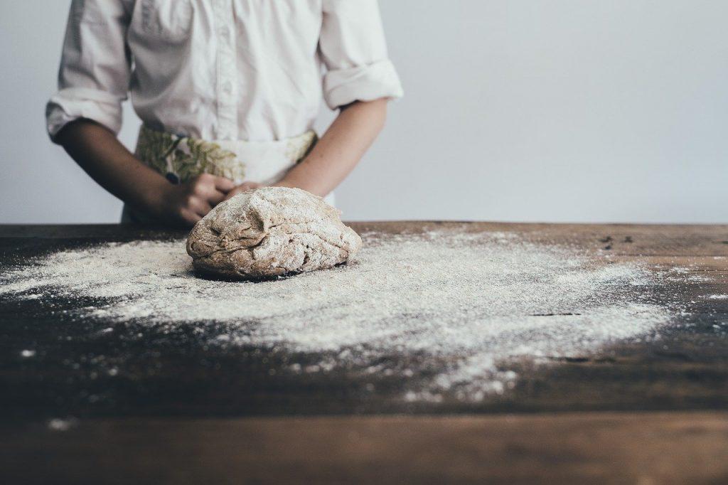 Grands moulins de paris farine sur une table et boulanger qui pétri